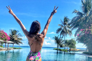 HOT Disha Patani poses in a floral swimsuit against a serene backdrop